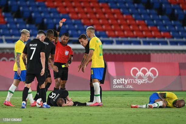 Salvadoran referee Ivan Barton gives a red card to Germany's midfielder Maximilian Arnold after he fouled Brazil's defender Dani Alves during the...