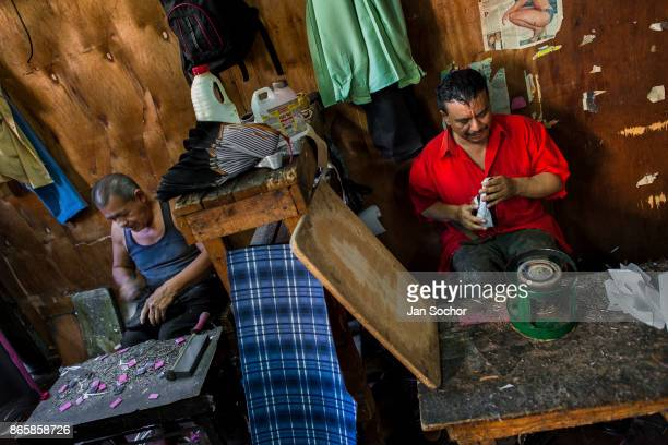 Salvadoran shoemakers work on new shoes attaching both insoles and outsoles at a shoe making workshop on November 16 2016 in San Salvador El Salvador