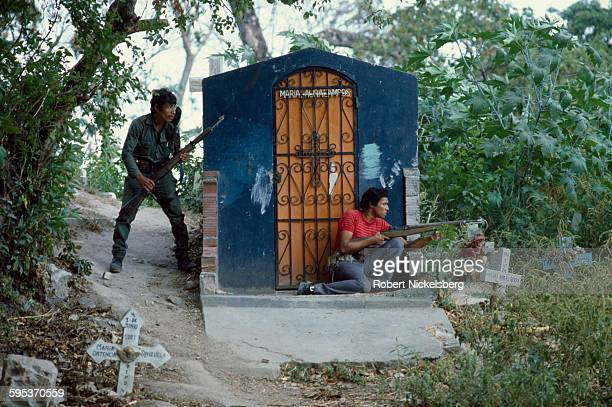 A Salvadoran soldier and a member of a local militia take cover in a neighborhood cemetery as they battle Farabundo Marti National Liberation Front...