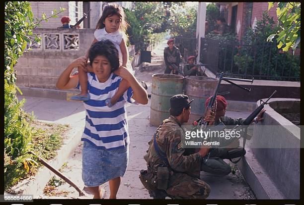 A Salvadoran woman and child evacuate from a neighborhood during a rebel offensive