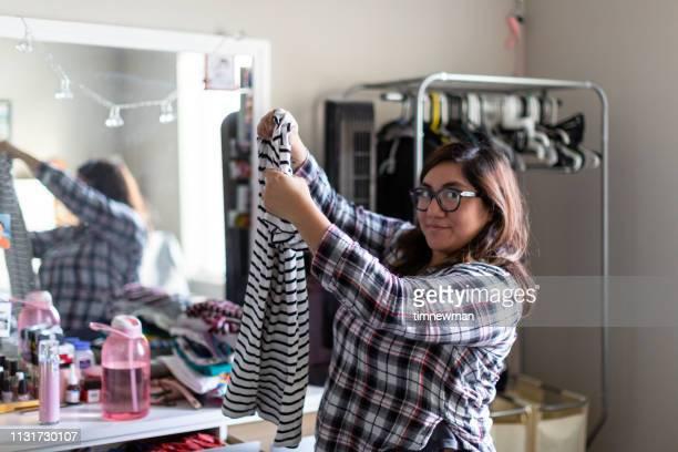 Salvadoran Woman Folding Laundry at Home