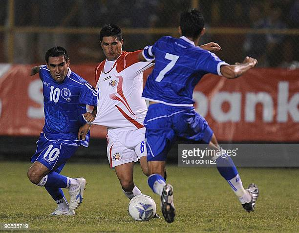 Salvadorean Eliseo Quintanilla and Ramon Sanchez vie for the ball with Costa Rican Christian Oviedo during their FIFA World Cup South Africa 2010...