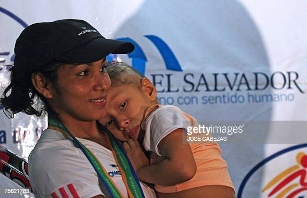 Salvadorean Gold medalist Cristina Lopez holds her daugther Monica before the start of a press conference at El Salvador international airport on...