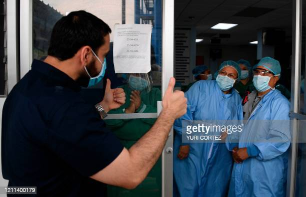 Salvadorean Health Minister Francisco Alabi gives the thumbs up to health workers of the San Rafael Hospital as they celebrate after a 16yearold...