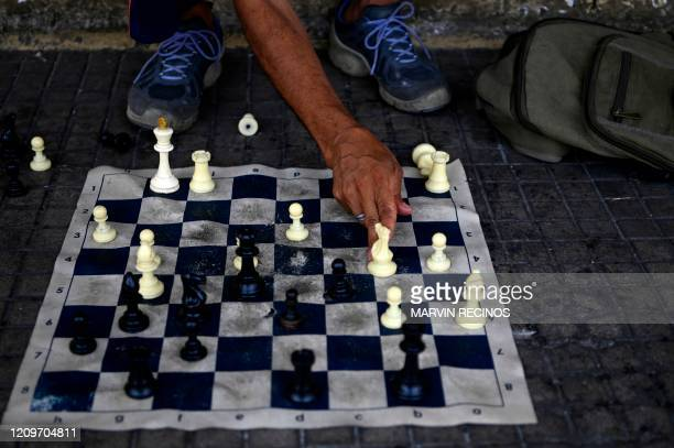 Salvadorean Luis Angel Carcamo who is homeless, wears a protective mask against the spread of the new coronavirus as he plays chess against himself...