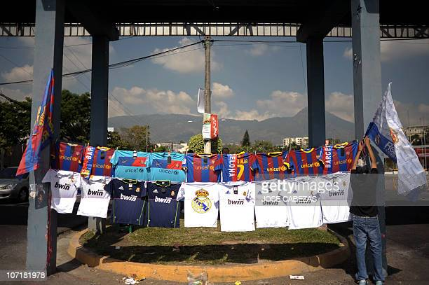 Salvadorean Manuel Gonzalez displays jerseys for sale of Barcelona Football Club and Real Madrid Football Club in San Salvador, on November 26, 2010....