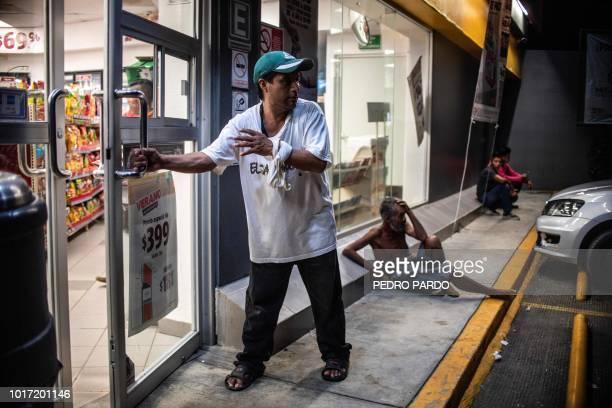 A Salvadorean migrant opens the door of a store to beg for money in Escuintla Chiapas state Mexico on August 10 2018
