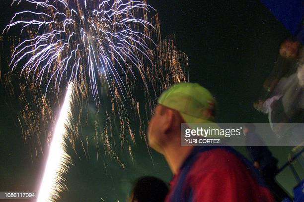 A Salvadorean observes the fireworks 23 November 2002 in the Flor Blanco Stadium during the opening ceremony of the Central American and Caribbean...