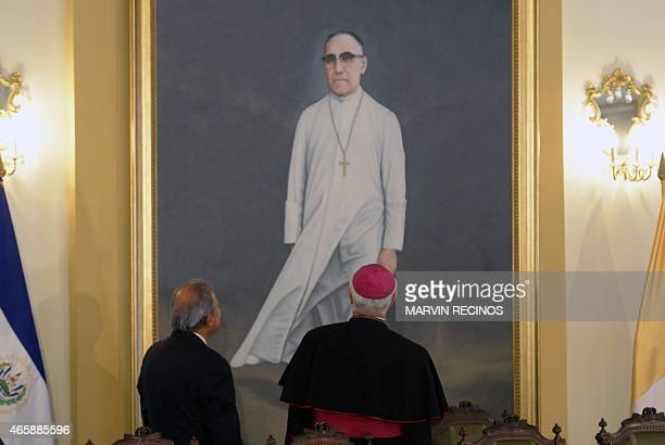 Salvadorean President Salvador Sanchez Ceren and Vatican official Italian Archbishop Vincenzo Paglia look at a painting of the late Archbishop Oscar...