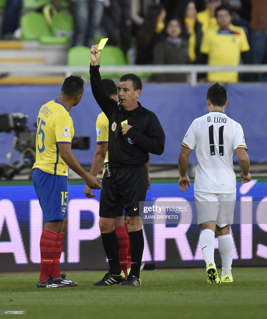 Salvadorean referee Joel Aguilar shows a yellow card to Ecuador's midfielder Pedro Quinonez during their 2015 Copa America football championship match, in Valparaiso, Chile, on June 15, 2015. AFP PHOTO / JUAN BARRETO