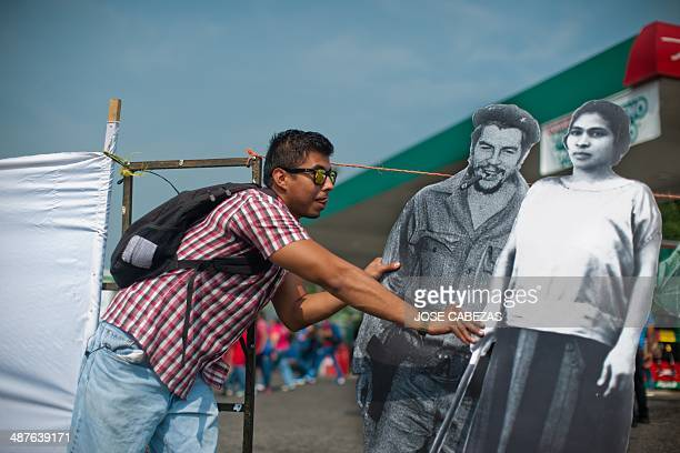 A Salvadorean worker poses next to a portraits of Ernesto Che Guevara and the historical Salvadorean women rights leader Prudencia Ayala as he takes...