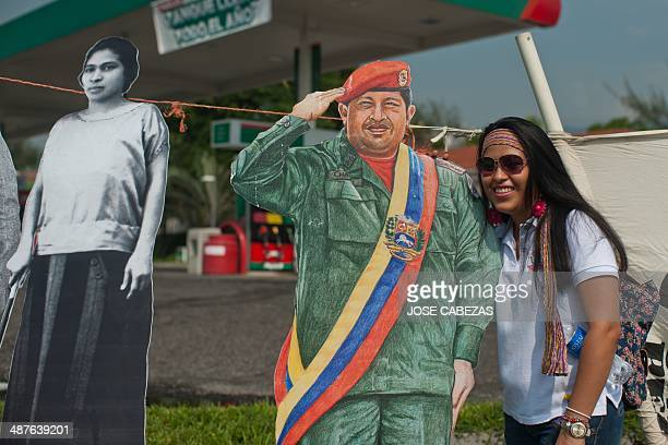 A Salvadorean worker poses next to portraits of late Venezuela President Hugo Chavez and the historical Salvadorean women rights leader Prudencia...