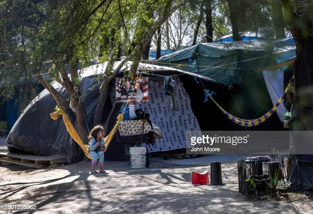 Salvadorian girl sits near a Biden-Harris campaign poster inside a camp for asylum seekers on February 07, 2021 in Matamoros, Mexico. Many of the...
