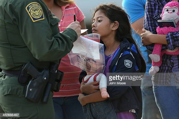 Salvadorian immigrant Stefany Marjorie watches as a US Border Patrol agent records family information on July 24 2014 in Mission Texas Like most of...