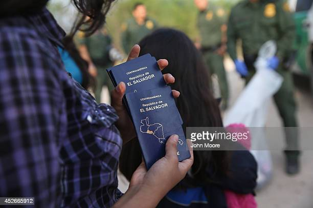 Salvadorian minor carries her family's passports after crossing the Rio Grande from Mexico into the United States on July 24 2014 in Mission Texas...