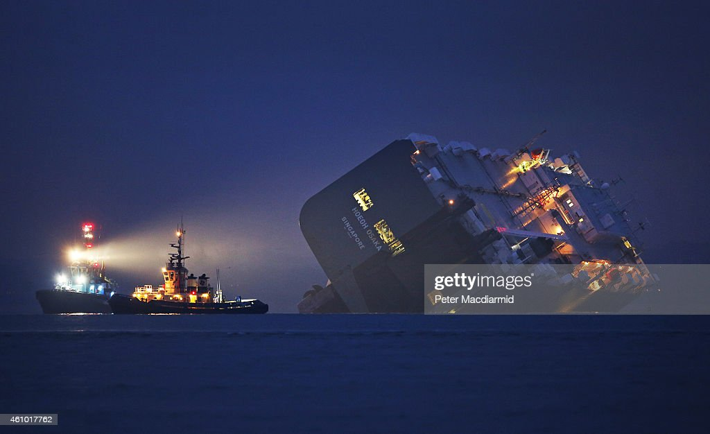 A salvage tug lights the hull of the stricken Hoegh Osaka cargo ship after it ran aground on a sand bank in the Solent on January 4, 2015 in Cowes, England. The cargo ship ran aground on Bramble Bank after leaving Southampton bound for Germany. All 25 crew members were rescued overnight.