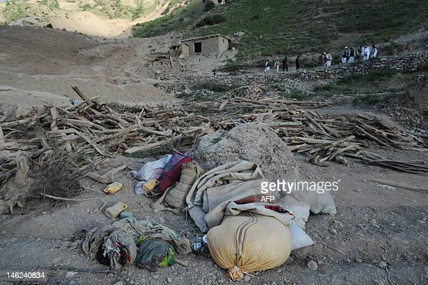 Salvaged belongings are seen as Afghan villagers search for earthquake victims past a collapsed house in a village at Burka district the worsthit...