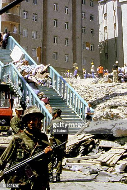 Salvaged Personal Belongings Are Piled On The Stairs Of An Overpass While Soldiers Keep The Curious Away As Rescue Workers Look For Survivors Under...