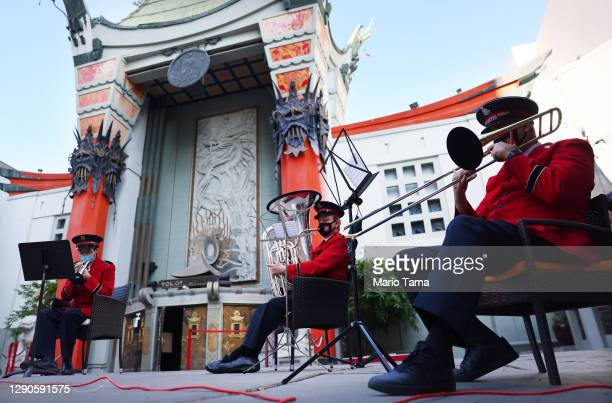 Salvation Army band members wear face masks while performing during a drive-thru red kettle donation collection in front of the TCL Chinese Theatre...