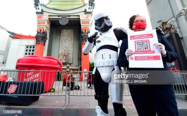Salvation Army member holds a copy of a QR code while posing with Hollywood impersonator dressed as a Star Wars Storm Trooper in front of the TCL...