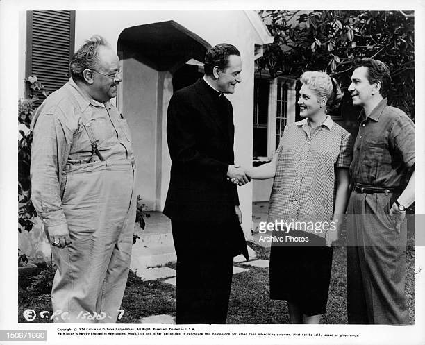 Salvatore Baccaloni greeting Judy Holliday and Richard Conte leaning in a scene from the film 'Full Of Life' 1956