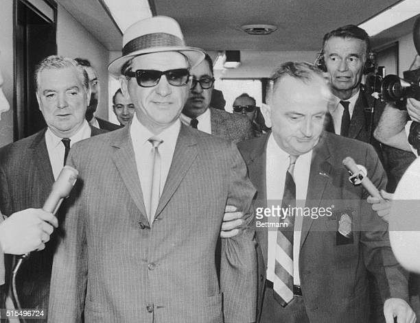 Salvatore 'Sam' Giancana in custody of an unidentified US Marshall after he was ordered jailed by a Federal District Judge here 6/1 for refusing to...
