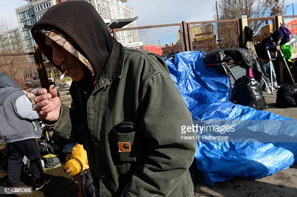 Salvatore who gave only his first name smokes a cigarette on the corner along Park Ave West and Lawrence street in Denver Colorado on March 7 2016 in...