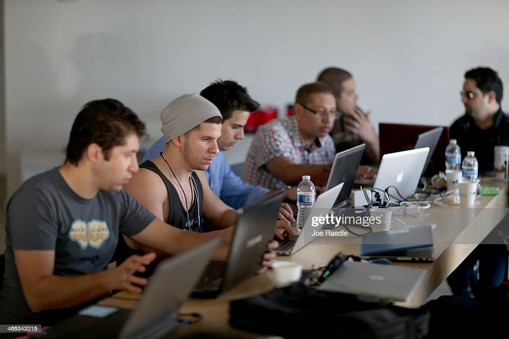 Salvi Pascual (L) and Daniel Arzuaga (2nd L) use their computers to write code for a program named Apretaste that would connect internet services like Craigslist, Google Maps and Wikipedia to Cuba via email so people living in Cuba would have access during the Hackathon for Cuba event on February 1, 2014 in Miami, Florida. The hackathon brought together experts and programmers to devise innovative technology solutions aimed at strengthening communications and information access in Cuba. The event is organized by Roots of Hope with support from the John S. and James L. Knight Foundation.