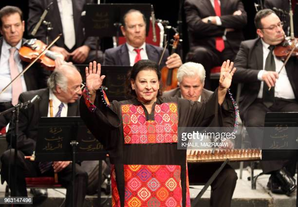 Salwa alAas a 74yearold Jordanian singer of Palestinian origin waves to the crowd on stage during a concert with the Beit alRowwad ensemble at...