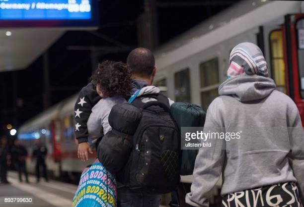 Salzburg Eine Fluechtlingsfamilie auf einem Bahnsteig vor einem Zug in Richtung Deutschland