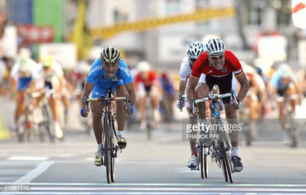 Italian Paolo Bettini crosses the finish line of the men's road cycling crown of the 2006 Cycling World championships followed by Germany's Erik...