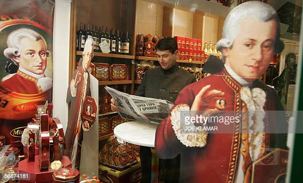 Mozart store owner offering endless varieties of sweets and souvenirs takes a quite moment to read a newspaper on the eve of the birthday of famous...