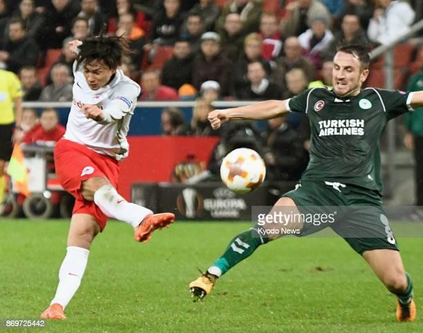 Salzburg striker Takumi Minamino shoots past Konyaspor midfielder Ali Camdali in the second half of their Europa League match at Stadion Salzburg in...