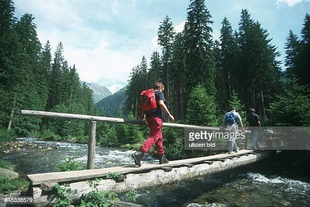 Salzburger Land: Wanderer im Lessachtal gehen über eine schmale Brücke über einen Bach - 1999