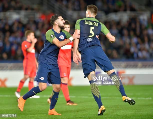 FC Salzburg's Croatian defender Duje CaletaCar is congratulated by teammate Israeli forward Munas Dabbur during the UEFA Europa League first leg...