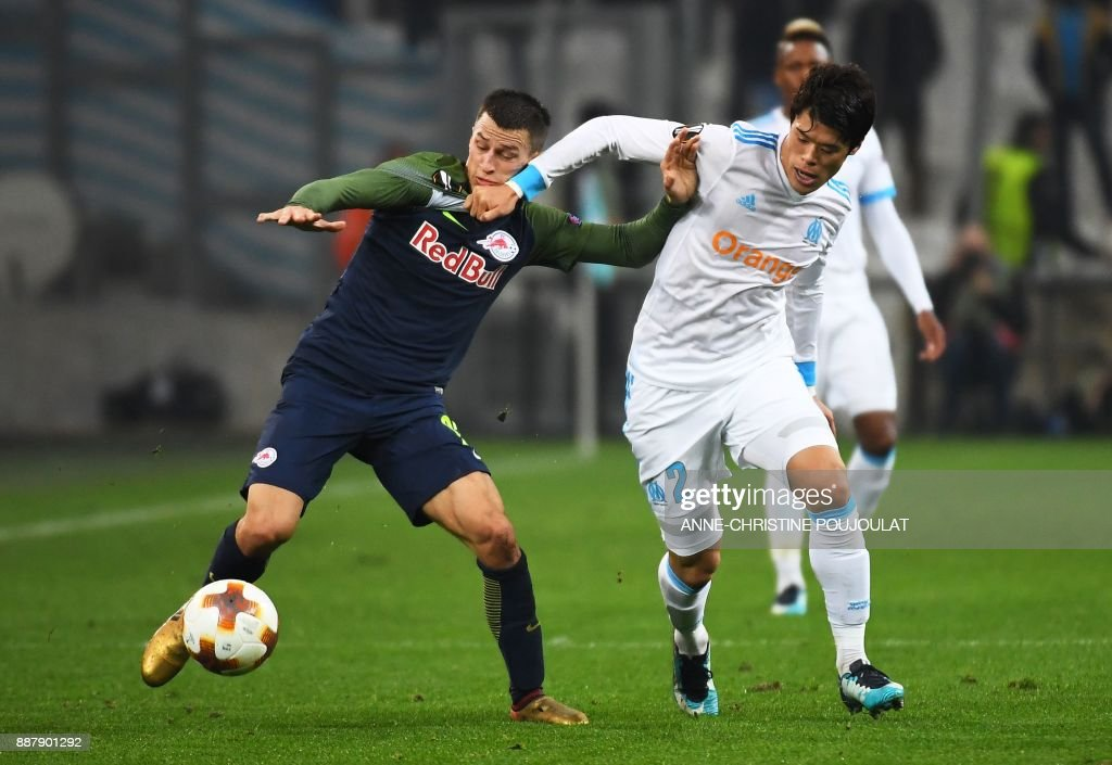 Salzburg's defender Stéfan Lainer (L) fights for the ball with Olympique de Marseille's Japanese defender Hiroki Sakai (R) during the UEFA Europa League football match Marseille vs Salzburg at the Velodrome stadium in Marseille, southern France on December 7, 2017. /
