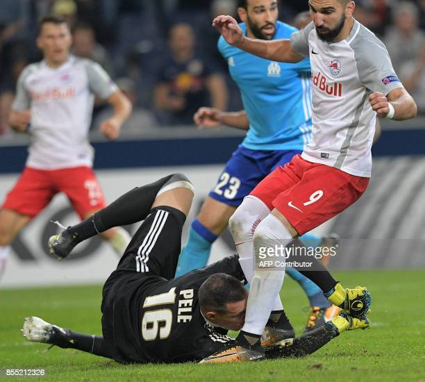 Salzburg's Israeli forward Munas Dabbur and Olympique de Marseille's French goalkeeper Yohann Pele vie for a ball during the UEFA Europa League group...