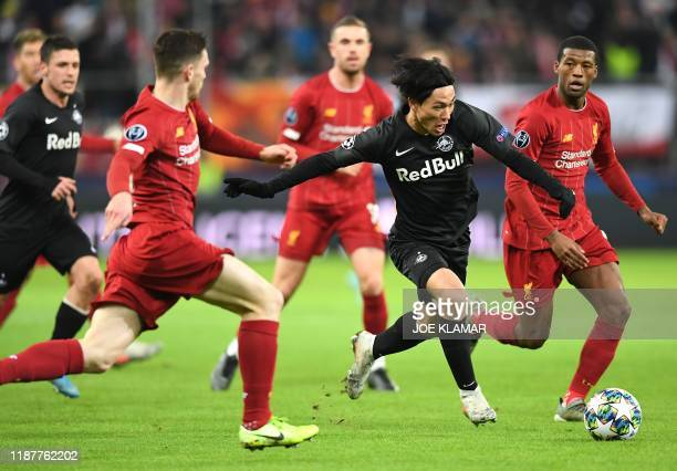 Salzburg's Japanese midfielder Takumi Minamino and Liverpool's Scotland's defender Andrew Robertson vie for the ball during the UEFA Champions League...