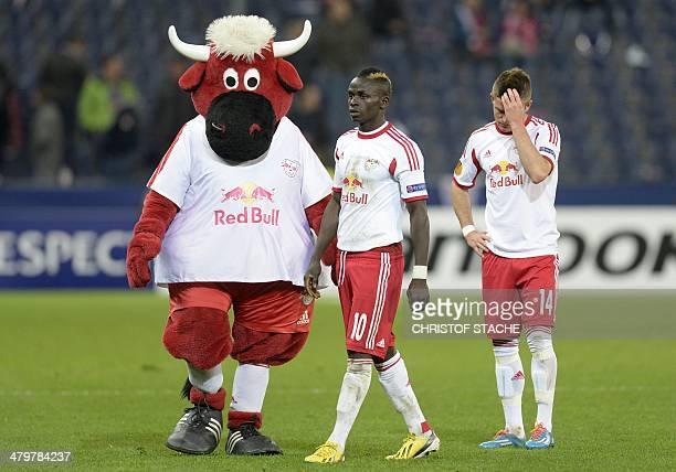 Salzburg's Norwegian midfielder Valon Berisha and Salzburg's Ghanaian midfielder Sadlo Mane leave the pitch with the team mascot after the last 16...