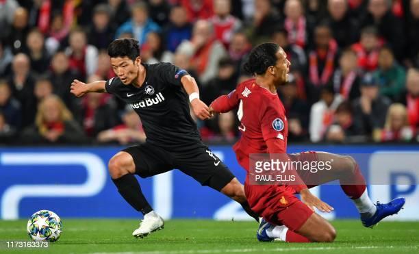 Salzburg's South Korean midfielder Hwang HeeChan beats Liverpool's Dutch defender Virgil van Dijk before scoring their first goal during the UEFA...