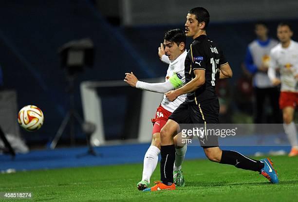 Salzburg's Spanish forward Jonathan Soriano scores a goal despite the defence of Zagreb's Croatian defender Arijan Ademi during the UEFA Europa...