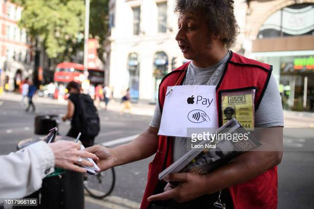 Sam advertises his acceptance of Apple Pay for purchasing copies of the homeless charity magazine 'The Big Issue' on August 17 2018 in London England...