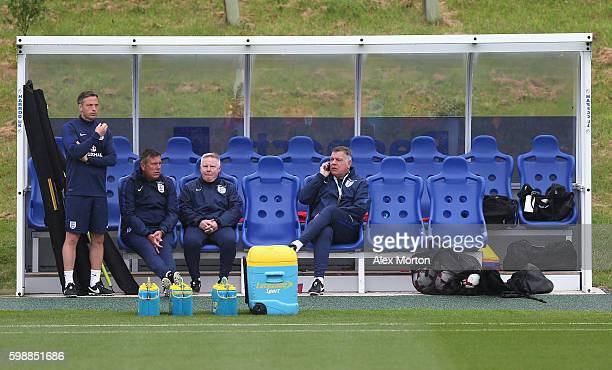 Sam Allardyce manager of England talks on the phone with assistant manager Sammy Lee and Craig Shakespeare during a training session at St George's...