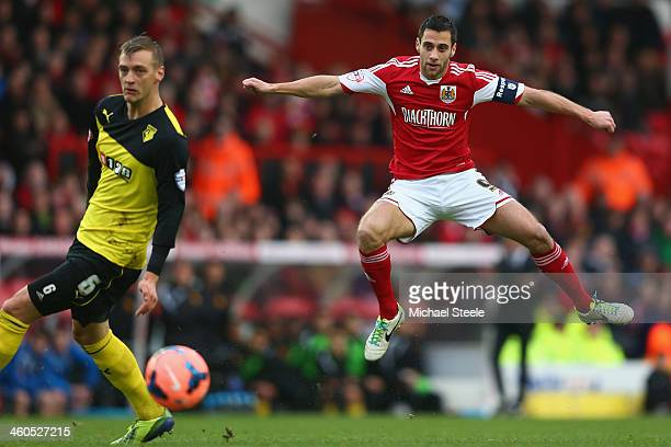 Sam Baldock of Bristol City shoots as Joel Ekstrand of Watford turns his back uring the Budweiser FA Cup Third Round match between Bristol City and...