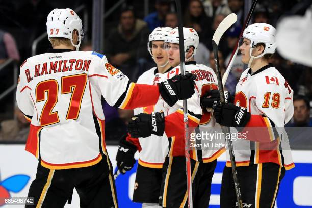 Sam Bennett is congratulated by Dougie Hamilton and Matthew Tkachuk of the Calgary Flames after scoring a goal during the first period of a game...