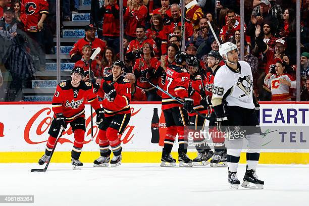 Sam Bennett Mikael Backlund and teammates of the Calgary Flames celebrate a goal against the Pittsburgh Penguins during an NHL game at Scotiabank...