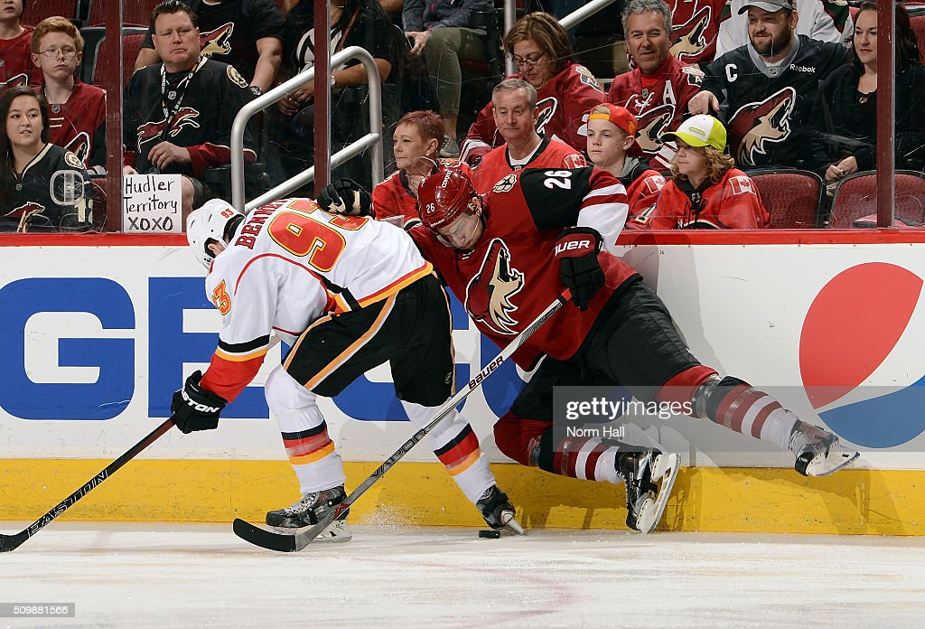 Sam Bennett #93 of the Calgary Flames and Michael Stone #26 of the Arizona Coyotes battle for the puck along the boards during the first period at Gila River Arena on February 12, 2016 in Glendale, Arizona.
