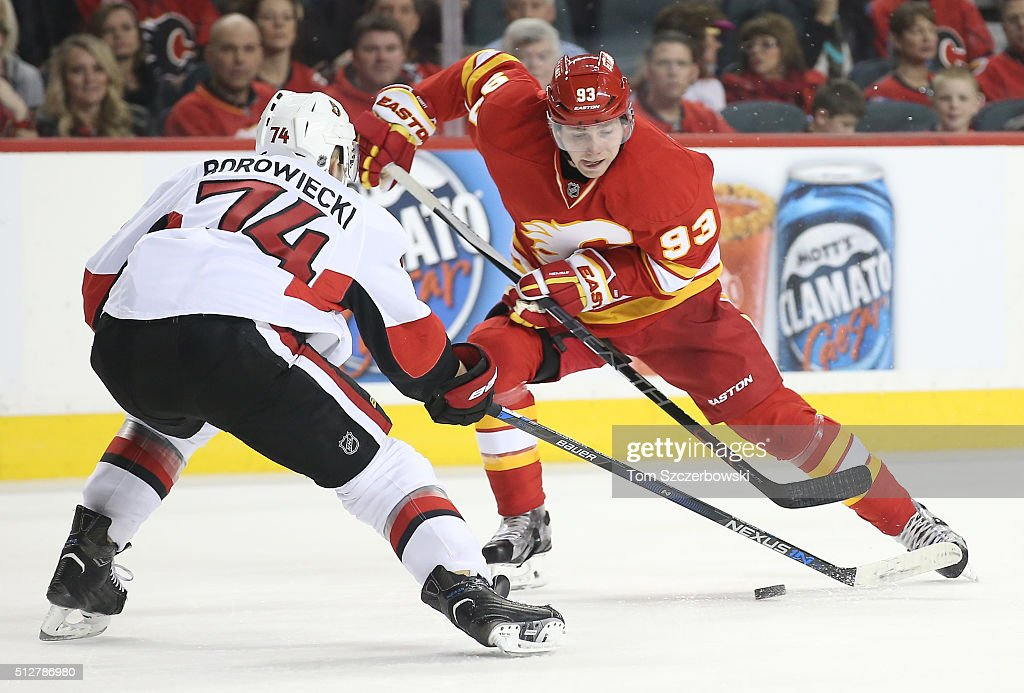 Sam Bennett #93 of the Calgary Flames attacks with the puck during their NHL game as Mark Borowiecki #74 of the Ottawa Senators defends at the Scotiabank Saddledome on February 27, 2016 in Calgary, Alberta, Canada.
