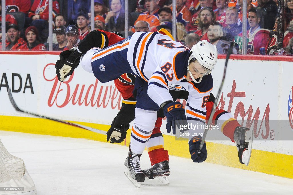 Sam Bennett #93 of the Calgary Flames collides with Matthew Benning #83 of the Edmonton Oilers during an NHL game at Scotiabank Saddledome on March 13, 2018 in Calgary, Alberta, Canada.