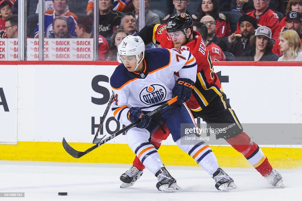 Sam Bennett #93 of the Calgary Flames fights Ethan Bear #74 of the Edmonton Oilers for the puck during an NHL game at Scotiabank Saddledome on March 13, 2018 in Calgary, Alberta, Canada.